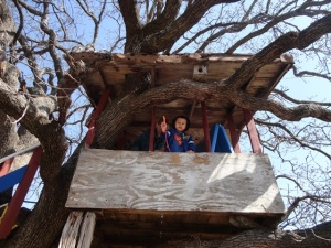 Noah waving his spring flower poem from the treehouse